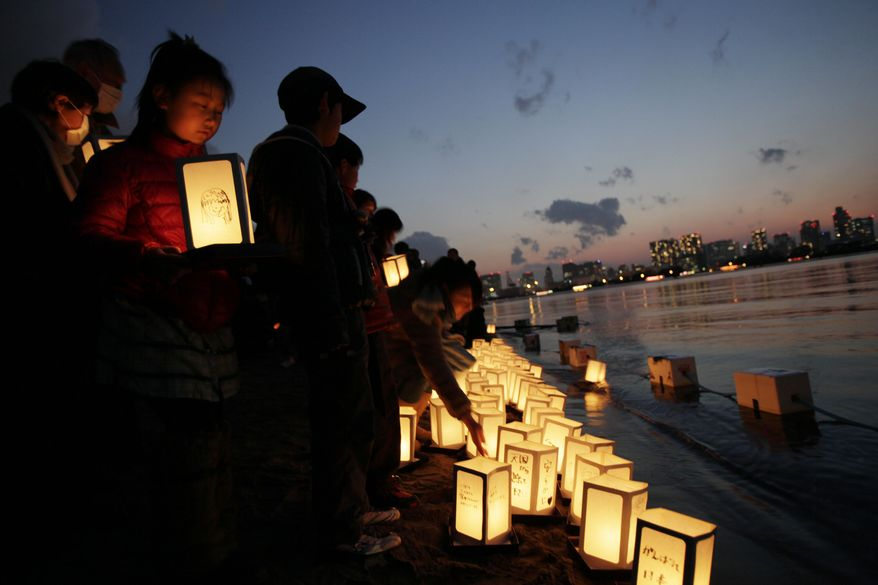 ** FILE ** A young girl waits her turn to release a lantern into the waters of Tokyo Bay on Sunday, March 11, 2012, to mark the first anniversary of the earthquake and tsunami that devastated northeastern Japan. (AP Photo/Greg Baker)