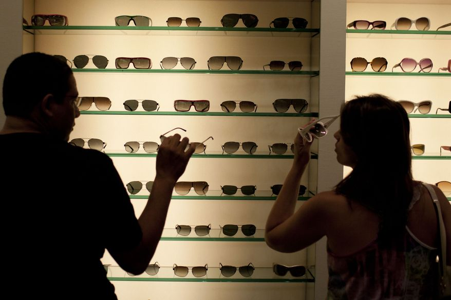 Milena Rangel (right) and her husband, Vanderson Rangel, both from Macae, Brazil, try on sunglasses in Fort Lauderdale, Fla., on Tuesday, March 6, 2012. Brazilian travelers spend more per capita than any other visitors to the United States. (AP Photo/Felipe Dana)