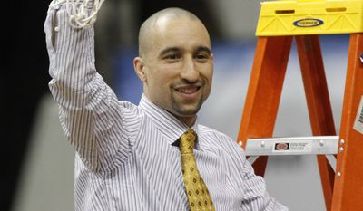 Virginia Commonwealth head basketball coach Shaka Smart waves the net after winning the Colonial Athletic Association Championship at the Coliseum in Richmond, Va., Monday, March 5, 2012. VCU beat Drexel 59-56. (AP Photo/Steve Helber)