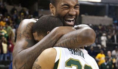 Norfolk State center Kyle O'Quinn (10) hugs teammate Kris Brown (22) after Norfolk State won the NCAA Mid-Eastern Athletic Conference championship game over Bethune-Cookman in Winston-Salem, NC., Saturday, March 10, 2012. (AP Photo/Lynn Hey)