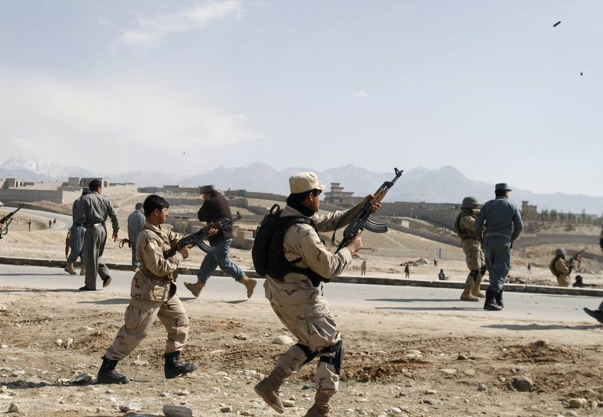 ** FILE ** Afghan security forces shoot in the air to disperse protesters outside American military base during an anti-U.S. demonstration in Mehterlam, Laghman province east of Kabul, Afghanistan, Thursday, Feb. 23, 2012. Afghan police fired shots in the air to disperse hundreds of protesters who tried to break into an American military base in the country's east to vent their anger over the Koran burnings incident. (AP Photo/Rahmat Gul)