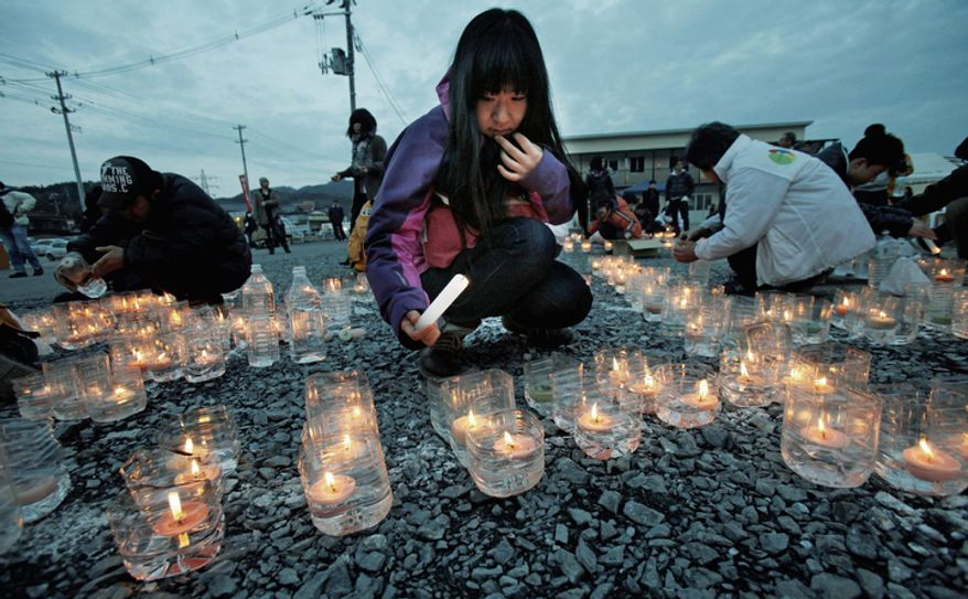 A girl lights candles in front of a temporary shopping complex in the earthquake and tsunami-devastated city of Kesennuma, Iwate prefecture, northeastern Japan, Sunday, March 11 2012, to mark the first anniversary of the massive disaster that devastated Japan one year ago. (AP Photo/Koji Sasahara)