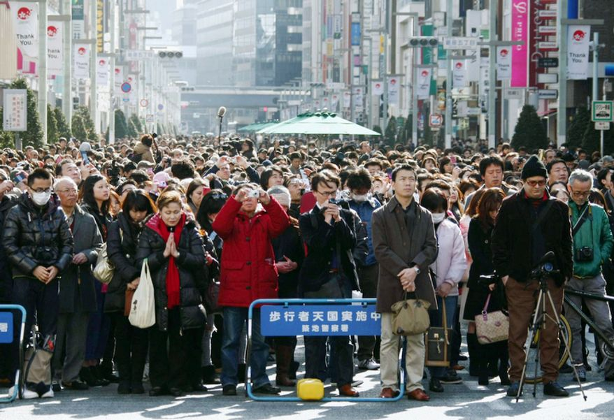 Pedestrians offer prayers at 2:46 p.m., the moment the magnitude-9.0 quake struck a year ago, for the disasters' victims, at Ginza district in Tokyo, Japan, on Sunday, March 11, 2012. The massive earthquake and tsunami that struck the nation a year ago, killed just over 19,000 people and unleashing the world's worst nuclear crisis in a quarter century.  (AP Photo/Kyodo News)