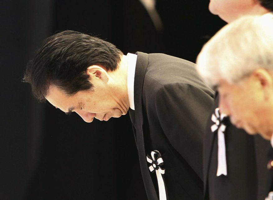 Former Japanese Prime Minister Naoto Kan bows to the altar during the national memorial service for the victims of the March 11, 2011, earthquake and tsunami in Tokyo, Japan on Sunday, March 11, 2012.  (AP Photo/Japan POOL)