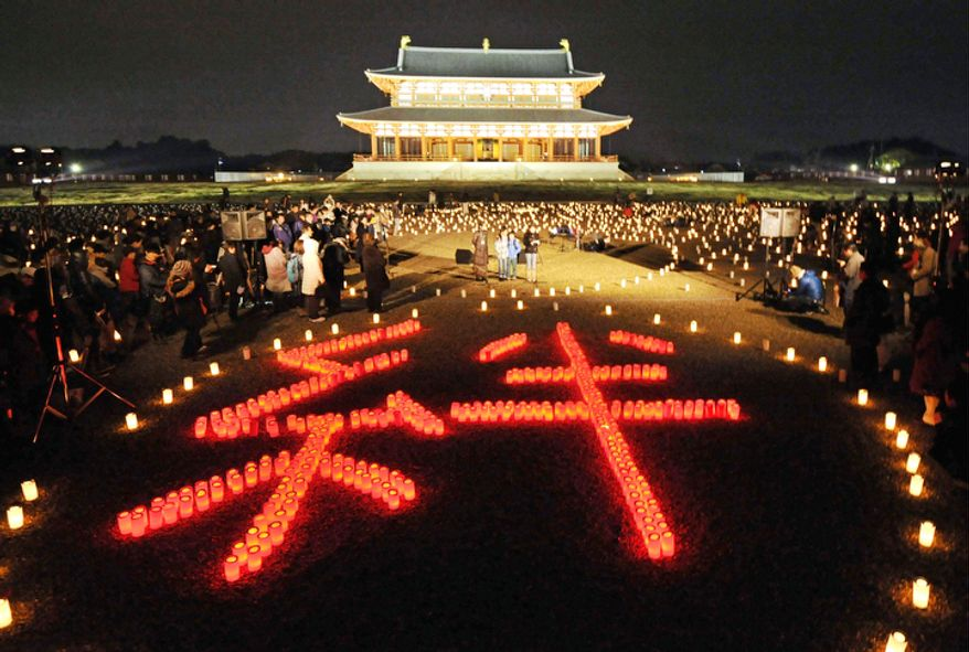 "People light candles in the shape of ""Kizuna,"" which means ""the inseparable bond between people"", during a memorial service for the victims of the March 11, 2011 earthquake and tsunami, near the site of Heijo Palace in Nara, central Japan, Sunday, March 11, 2012.  (AP Photo/Kyodo News)"