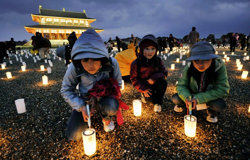 Children light candles during a memorial service for the victims of the March 11, 2011 earthquake and tsunami, near the site of Heijo Palace in Nara, central Japan, Sunday, March 11, 2012.   (AP Photo/Kyodo News)