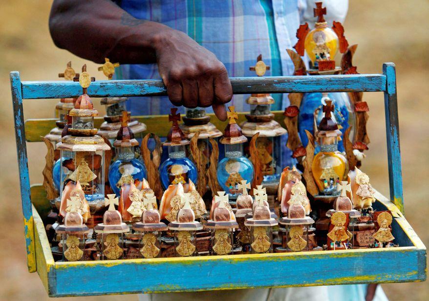 A vendor sells small statues of Cuba's patron saint, La Virgen de la Caridad del Cobre (Our Lady of Charity), during a Santeria ceremony at the annual Caribbean Festival in Loma del Cimarron. (Associated Press)