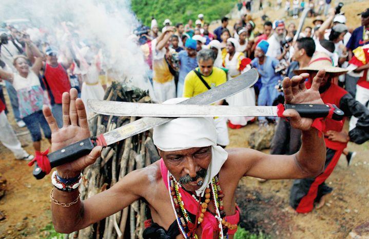 A Santero priest in 2010 holds machetes over his head as he moves around a fire during a Santeria ceremony at the annual Caribbean Festival in Loma del Cimarron, El Cobre, Cuba. (Associated Press) ** FILE **