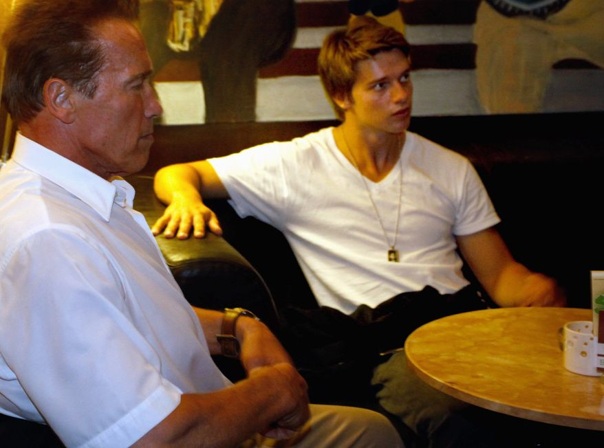 "Arnold Schwarzenegger and his son Patrick sit in a coffee bar in Graz, Austria, in October. Patrick Schwarzenegger, 18, tweeted Saturday that he had received stitches down his back following ""a little ski accident"" in Idaho. (Associated Press)"