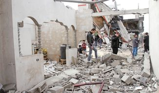 Palestinians inspect building rubble after an Israeli airstrike on Jabaliya in the Gaza Strip on Monday. Airstrikes killed two Palestinian militants and a schoolboy while Palestinian rocket squads barraged southern Israel. (Associated Press)