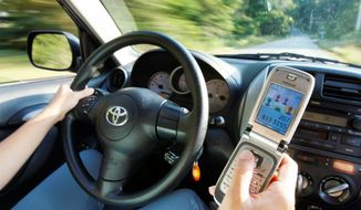 Drivers using cell phones and other devices, whether in the dashboard or hand-held, are the subject of distracted-driving debates. (Associated Press)