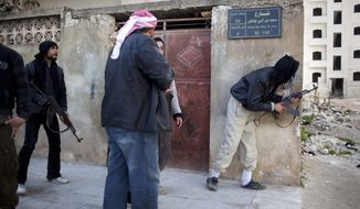 Free Syrian Army fighters take cover during fierce fighting against government troops in Idlib, Syria, on Saturday, March 10, 2012. (AP Photo/Rodrigo Abd)