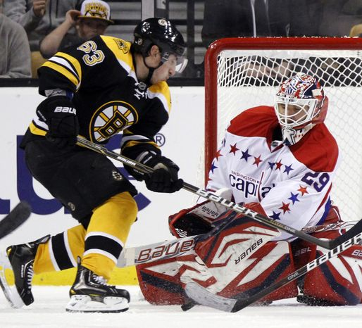 Washington Capitals goalie Tomas Vokoun (29) deflects the puck in front of Boston Bruins' Brad Marchand in the third period of an NHL game in Boston, Saturday, March 10, 2012. The Capitals won 4-3. (AP Photo/Michael Dwyer)