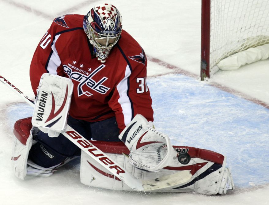 Washington Capitals goalie Michal Neuvirth (30) block a shot during the first period of an NHL game against Toronto, Sunday, March 11, 2012, in Washington. (AP Photo/Carolyn Kaster)