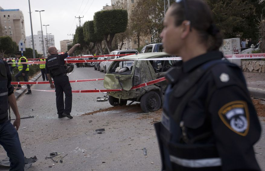 Israeli police officers patrol a site after a rocket fired by Palestinian militants from the Gaza Strip hit the city of Ashdod in Israel on March 12, 2012. (Associated Press)