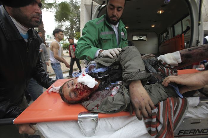 Palestinian medics wheel a wounded man to the treatment room of Shifa hospital on March 12, 2012, following an Israeli air strike in Gaza City. (Associated Press)