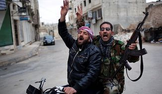 In this photo from March 11, 2012, Syrian rebels celebrate the destruction of a military tank during a day of heavy fighting with Syrian government forces in Idlib, north Syria. Syrian activists said that pro-government gunmen have killed several people including children in a rebel stronghold recaptured by the government in the embattled central city of Homs. (Associated Press)