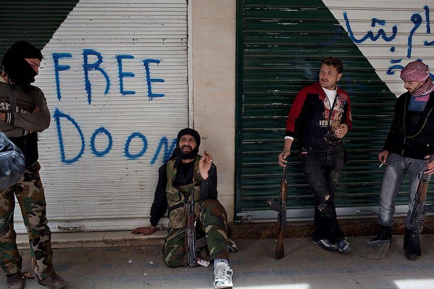 In this photo from March 11, 2012, Syrian rebels rest during a day of heavy fighting with Syrian government forces in Idlib, north Syria. Syrian activists said that pro-government gunmen have killed several people including children in a rebel stronghold recaptured by the government in the embattled central city of Homs. (Associated Press)