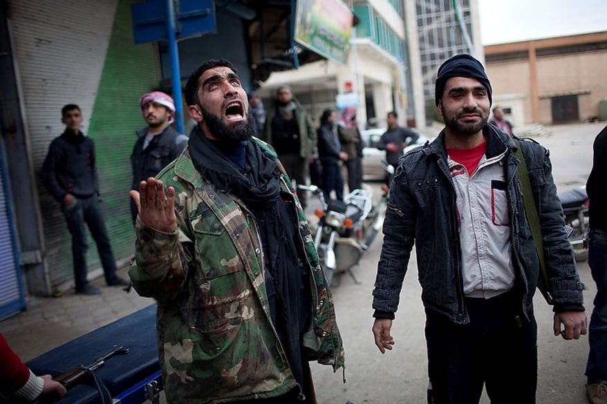 In this photo from March 11, 2012, a Syrian rebel reacts after learning at least four comrades died during clashes with Syrian government forces in Idlib, north Syria. (Associated Press)