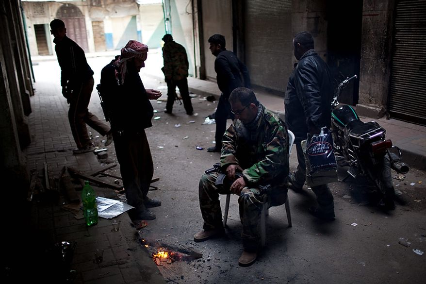 In this photo from March 11, 2012, Free Syrian Army fighters pause for a moment in between fierce firefights with Syrian Army in the town of Idlib, north Syria. (Associated Press)