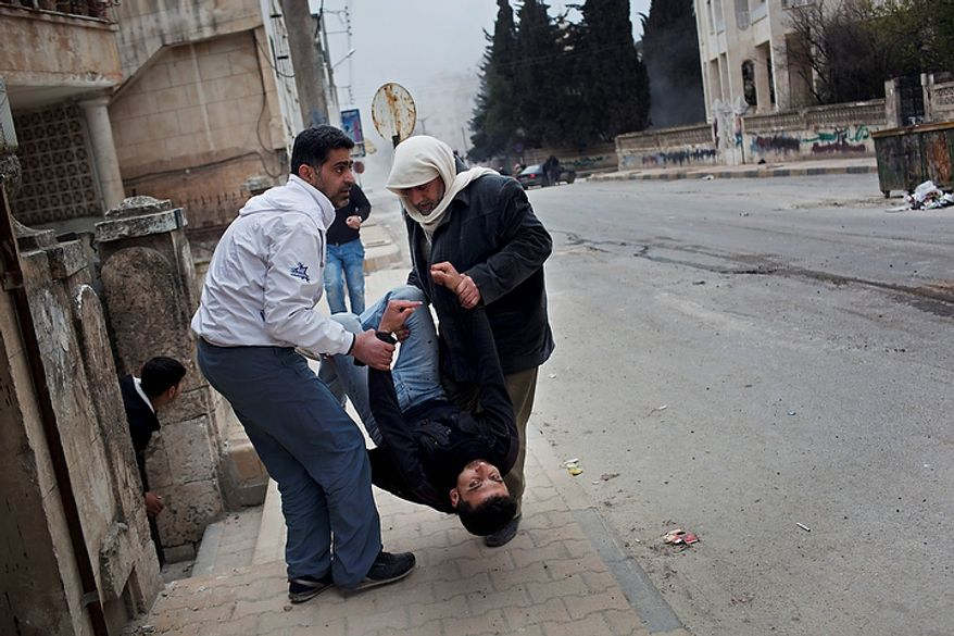In this photo from March 11, 2012, a Free Syrian Army fighter is assisted by comrades seconds after being wounded by fragments of an exploding shell in Idlib, north Syria. (Associated Press)