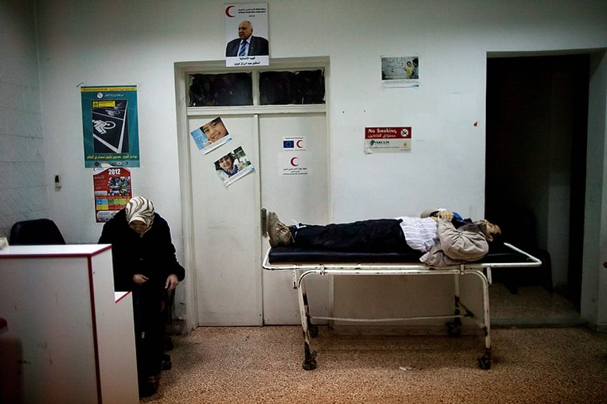 In this photo from March 11, 2012, the wife of Mohammed Halak slumps in a chair next to his body as she mourns the death of her husband, who was killed during fighting between Free Syrian Army fighters and the Syrian Army in Idlib, north Syria. Scores of people have been reported dead during clashes between government forces and Free Syrian Army fighters. (Associated Press)