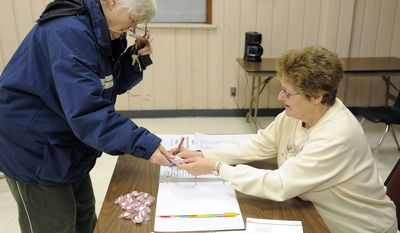 Margaret Henze (left) hands her identification to election inspector Judy Wise on Tuesday, Feb. 21, 2012, at the Lakeview Community Center in Racine, Wis., during a school board primary election. (AP Photo/Journal Times, Scott Anderson)