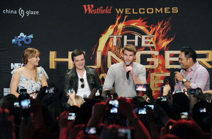 """Jennifer Lawrence, Josh Hutcherson and Liam Hemsworth (from left) talk to fans in Century City, Calif., about filming """"The Hunger Games,"""" during a publicity stop on March 3. The film opens in theaters March 23. (Associated Press)"""