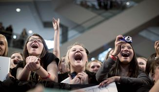 "Fans cheer the stars from the film ""The Hunger Games,"" during an appearance at the Microsoft store at the Mall of America in Minneapolis on Friday. The film, based on the young adult book series by Suzanne Collins, had its world premiere in Los Angeles on Monday. (Minneapolis Star Tribune via Associated Press)"