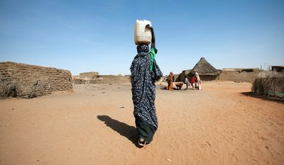 In this photo taken Tuesday, Feb. 21, 2012 and released by the United Nations African Union Mission in Darfur (UNAMID), Kaltoum Yakoub Issa, 19, carries a water jerry can to make bricks for her new house in Abu Shouk camp for internally displaced people (IDP) in North Darfur, Sudan. (AP Photo/UNAMID, Albert Gonzalez Farran)