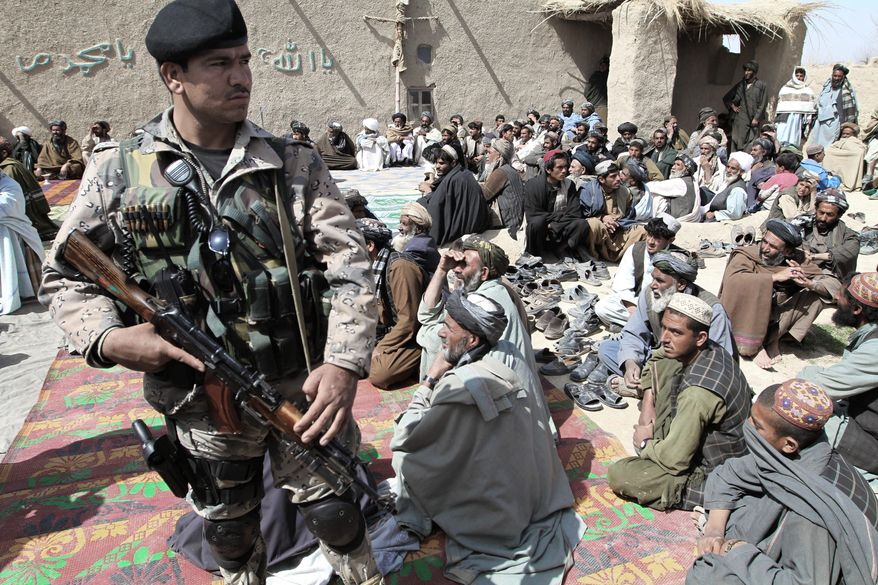 An Afghan security guard keeps watch Tuesday as villagers listen to a speech by an Afghan official. They are part of a delegation attending a prayer ceremony for civilian victims in a killing spree Sunday, possibly by a U.S. soldier, in Kandahar province. (Associated Press)