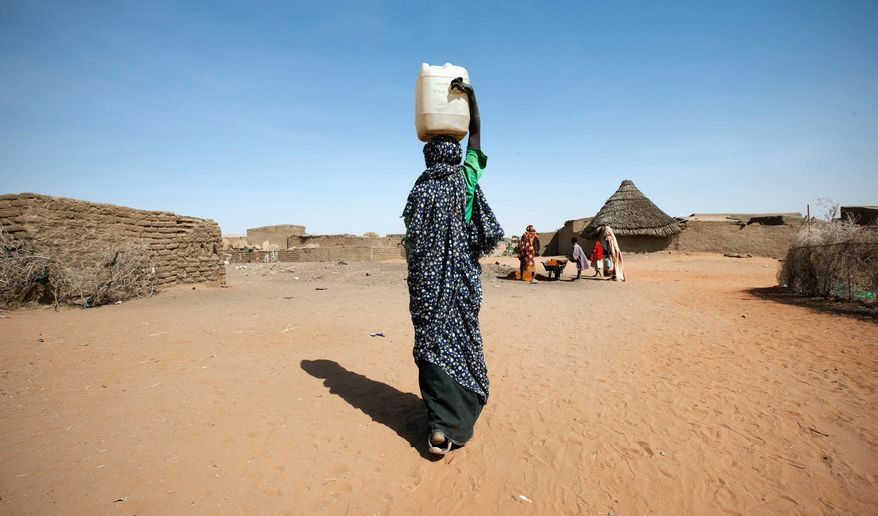 ASSOCIATED PRESS A young woman carries a water canister to make bricks for her new house in a camp for internally displaced people in North Darfur, Sudan. Severely injured and disfigured 10 years ago by the long-running violence in the region of the African nation, she is trying to rebuild her life with her sister in the refugee camp.