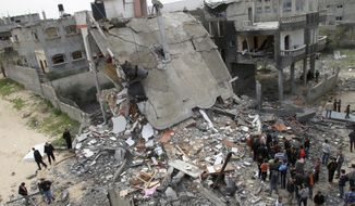 Palestinians inspect the rubble of a building destroyed in an Israeli airstrike in Jabaliya, Gaza Strip, on Monday, March 12, 2012. (AP Photo/Adel Hana)