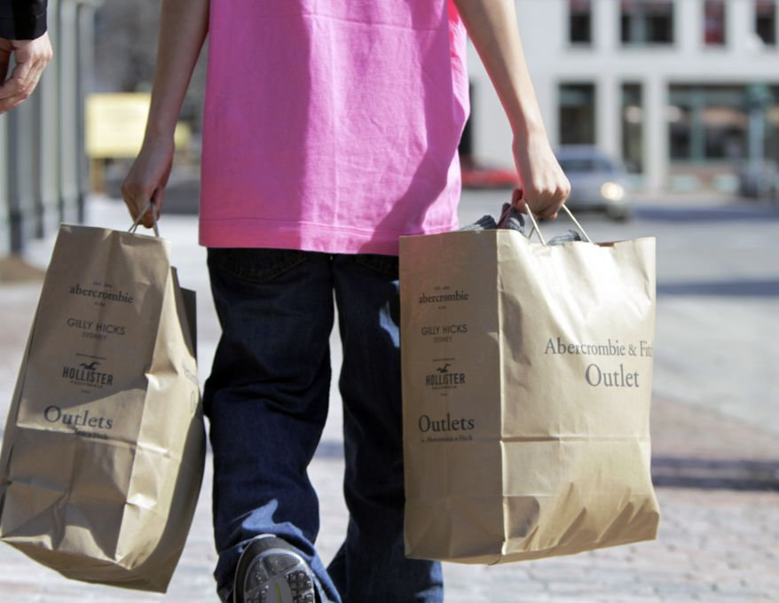 A shopper carries bags of merchandise in Freeport, Maine, on Monday, March 12, 2012. (AP Photo/Pat Wellenbach)