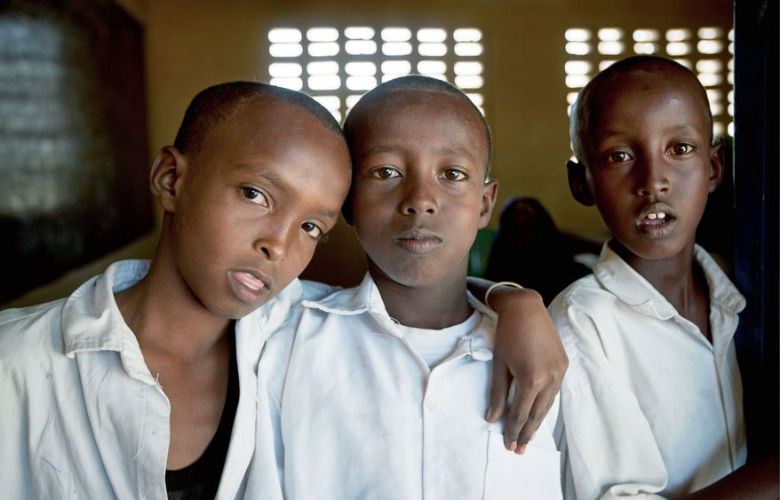 Somali schoolboys take a break from class in Dhobley, a town under the control by Kenyan military and Somali government forces. Many children in Somalia are uneducated and are forced to join armed groups such as al-Shabab. (Associated Press)