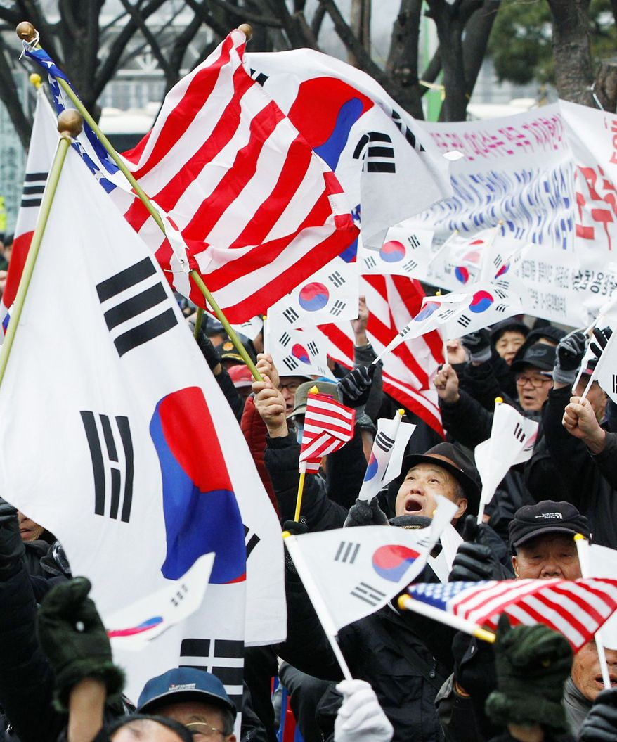 South Korean supporters of the free-trade agreement celebrate Wednesday near the U.S. Embassy in Seoul. Proponents of the long-delayed accord say it will boost business and the half-century alliance between the countries. (Associated Press)