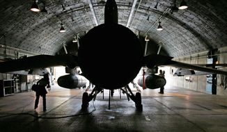 An Israeli air force F-16I fighter plane sits at the ready in a hangar at Ramon Air Force Base in southern Israel. The F-16I, which is equipped with external fuel tanks, is reportedly capable of reaching Iranian airspace without refueling. It could carry U.S.-made bunker-busting bombs that drill below ground before exploding. (Associated Press)