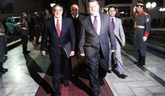 Afghan Interior Minister Bismillah Mohammadi (right) walks with U.S. Secretary of Defense Leon Panetta to the interior ministry in Kabul, Afghanistan, on March 14, 2012. (Associated Press)