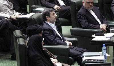 Iranian President Mahmoud Ahmadinejad (center) listens March 14, 2012, to conservative lawmaker Ali Motahari (not shown), a prominent opponent of the president, as he reads out a series of questions to Ahmadinejad in an open session in parliament in Tehran. (Associated Press)