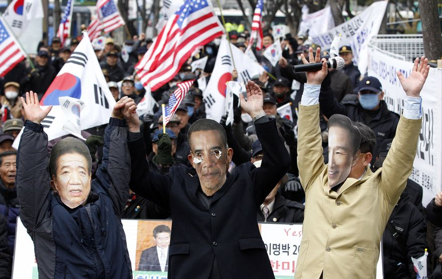 South Korean activists wearing masks of U.S. President Obama (center), South Korean President Lee Myung-bak (right) and the late South Korean President Roh Moo-hyun cheer to celebrate the free-trade agreement between South Korea and the United States during a rally near the U.S. Embassy in Seoul on Wednesday, March 14, 2012. (AP Photo/Lee Jin-man)
