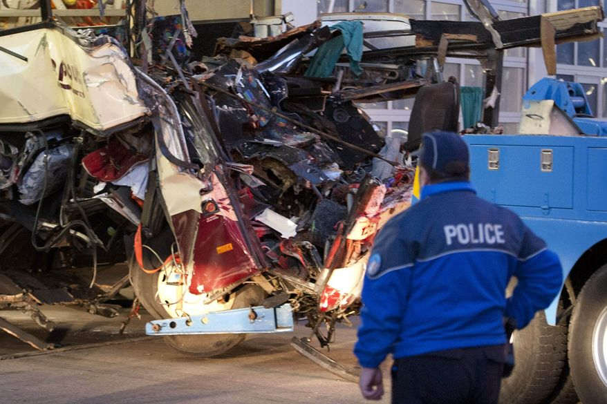 A police officer works at the wreckage of a tourist bus from Belgium at the accident site in a tunnel of the A9 highway near Sierre, western Switzerland, early Wednesday, March 14, 2012. (AP Photo/Keystone, Laurent Gillieron)