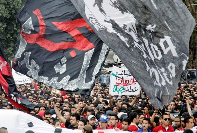 """Thousands of Egyptian activists and soccer fans on Thursday participate in a march from the headquarters of the al-Ahly club toward the Egyptian general prosecutor's office in downtown Cairo to protest against what they say is the slow pace of procedures taken by the government to find and hold accountable those responsible for soccer violence in Port Said that claimed scores of victims. Arabic on the banner reads, """"The glory for martyrs."""" (Associated Press)"""