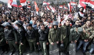 Syrian riot police stand guard during a rally Thursday supporting President Bashar Assad in Damascus. Thousands poured into the streets of the Syrian capital in a show of support for the Assad regime as soldiers tightened their siege in opposition areas on the one-year anniversary of the country's uprising. (Associated Press)