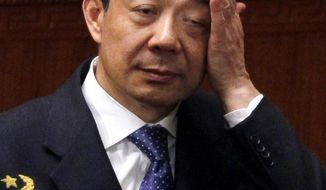 ** FILE ** Bo Xilai, then the Communist Party secretary in Chongqing, rubs his face during a session of the National People's Congress in Beijing on Friday, March 9, 2012. (AP Photo/Ng Han Guan)