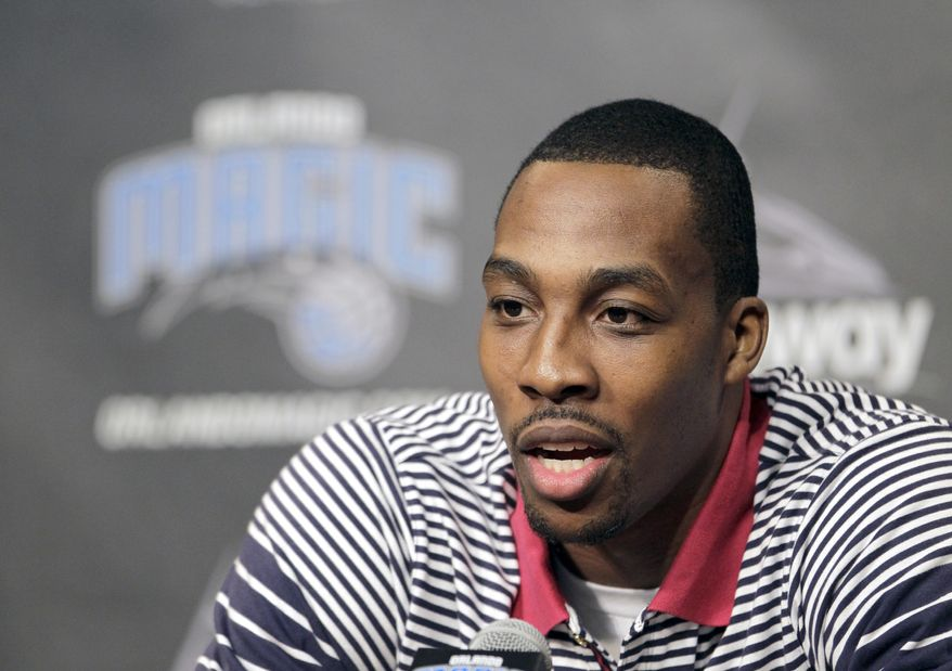 Orlando Magic center Dwight Howard answers questions during a news conference,Thursday, March 15, 2012, in Orlando, Fla. Howard signed papers Thursday agreeing to waive the early termination option in his contract, guaranteeing he will be with the Magic at the beginning of the 2012-13 season. (AP Photo/John Raoux)