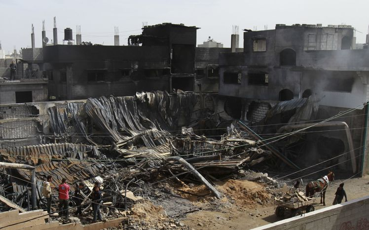 Palestinians inspect a warehouse which caught fire March 14, 2012, after an Israeli air strike nearby in Gaza City. (Associated Press)