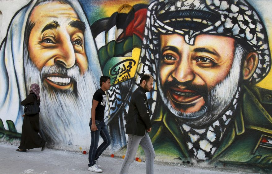 Palestinians pass by a mural of the late Palestinian President Yasser Arafat (right) and late Hamas founder and spiritual leader Sheik Ahmed Yassin in Gaza City on March 14, 2012. (Associated Press)
