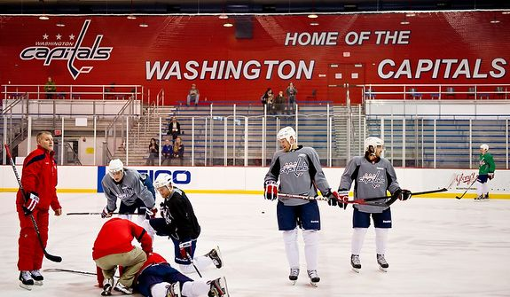 Teammates surround Washington Capitals left wing Alex Ovechkin (8) as he lays on the ice after a center ice collision with Washington Capitals right wing Mike Knuble (22) during a morning practice at Kettler Capitals Iceplex, Arlington, Va., March 15, 2012. Ovechkin stayed on the ice for two minutes and then sat on the bench for another three and a half minutes before leaving practice. (Andrew Harnik/The Washington Times)