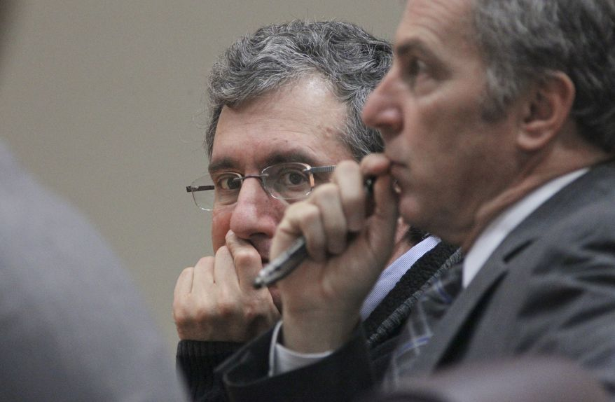 Defendant Hemy Neuman (left) and defense attorney Bob Rubin listen to the judge's instructions to the jury during Neuman's murder trial on Wednesday, March 14, 2012, in Decatur, Ga. (AP Photo/Atlanta Journal-Constitution, John Spink)