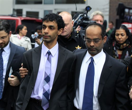 Dharun Ravi (center) is hugged by his father, Ravi Pazhani, on March 16, 2012, as they leave court in New Brunswick, N.J. Ravi, a former Rutgers University student accused of using a webcam to spy on his gay roommate's love life, was convicted of bias intimidation and invasion of privacy. (Associated Press)